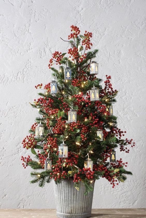 a vintage-inspired tabletop Christmas tree with berries, lights and tree-shaped mini lanterns is a lovely and bold idea