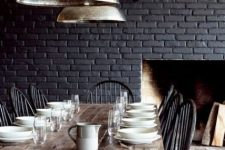 a vintage meets rustic dining room with a black brick wall, a wooden table and dark vintage chairs is very cozy