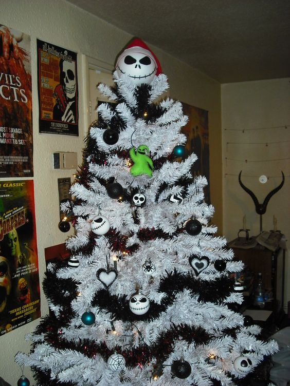 a white Christmas tree with black garlands, black and white ornaments, Jack Skellington ones and a Jack Skellinton topper
