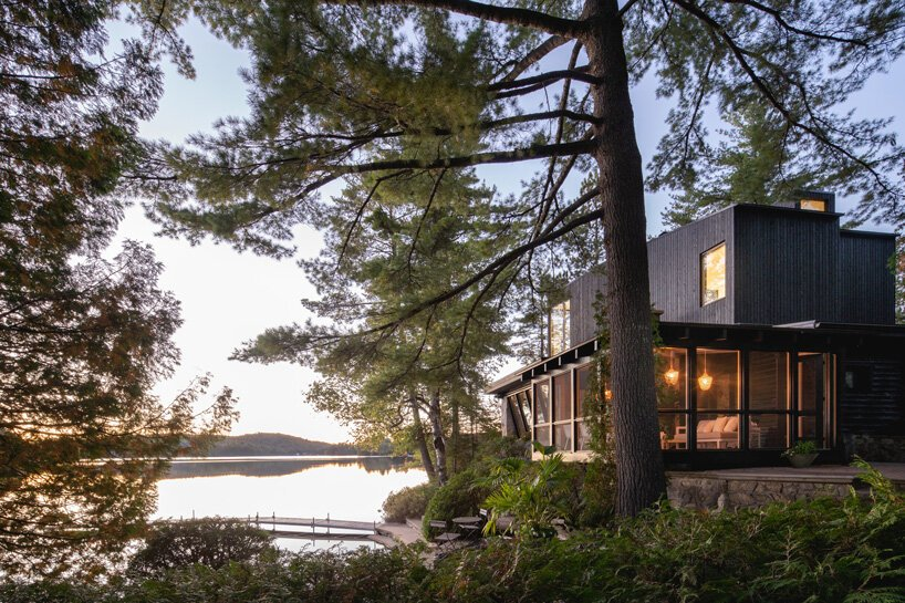 This rustic log cabin in Canada got an extension on top, it is clad with black timber to merge with nature