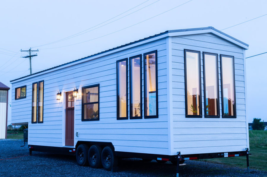 This tiny home on wheels is a very simple and clean house, with white facades and a metal roof plus lots of windows
