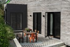 02 The exterior of the house is contrasting, dark and light, with a terrace with a wooden table and orange chairs