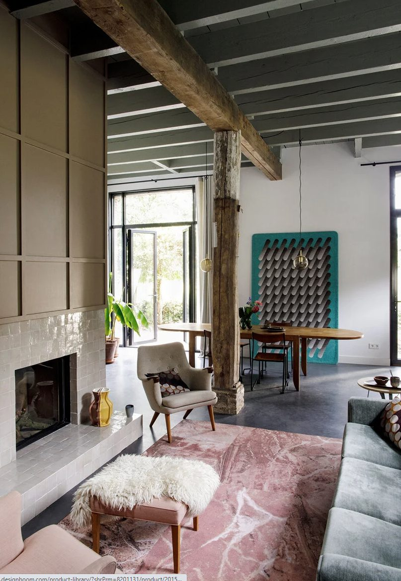 The living room is done with a fireplace clad with white tiles, a grey sofa, wooden beams and pillars, a dining space with an oval table is adjoined here