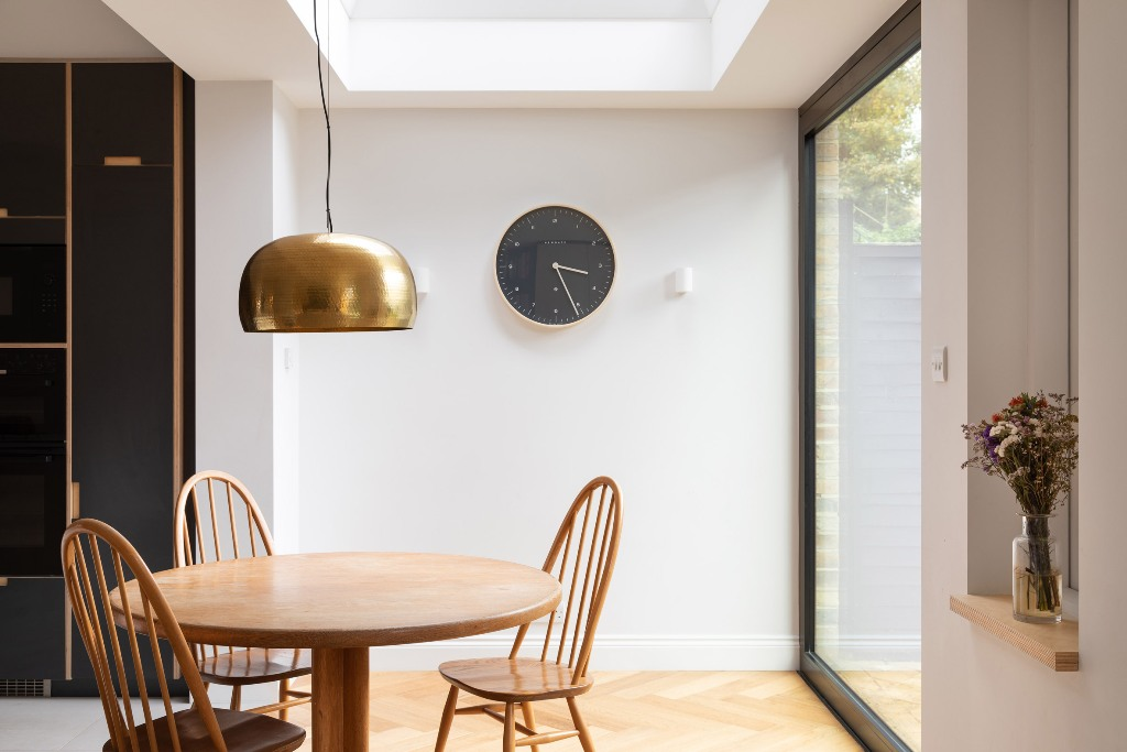 The dining space is located by the window, there's a pendant lamp and a skylight
