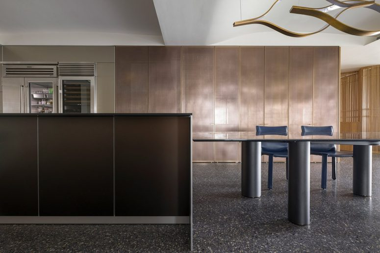 The kitchen is done with sleek dark and metallic cabinetry, there's a large table and a couple of blue chairs