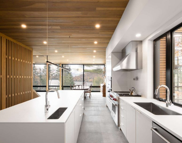 The kitchen is done with sleek white cabinets, a wooden ceiling and a concrete floor plus a wooden space divider