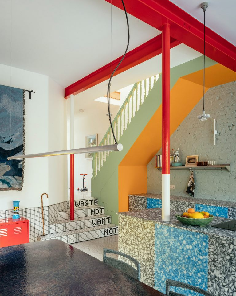 The kitchen is grey and blue, and you may see red and white pillars here that add color