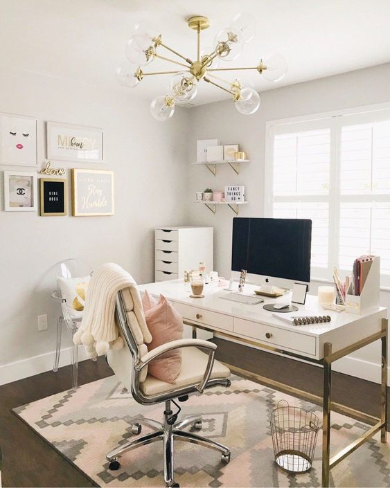 a glam and chic home office with gold touches and a comfy chair plus a cool girlish gallery wall