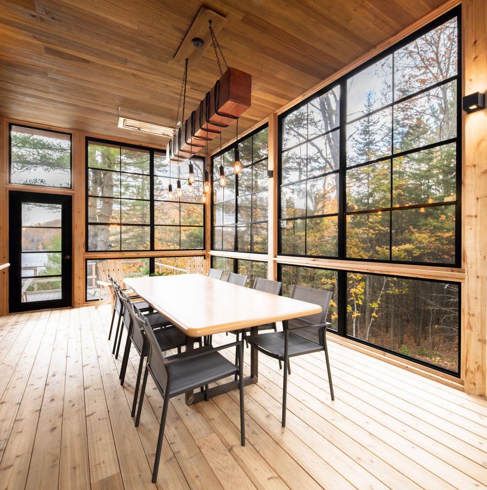 The dining space fully benefits from the views, with a wooden table, black meta chairs and an industrial chandelier
