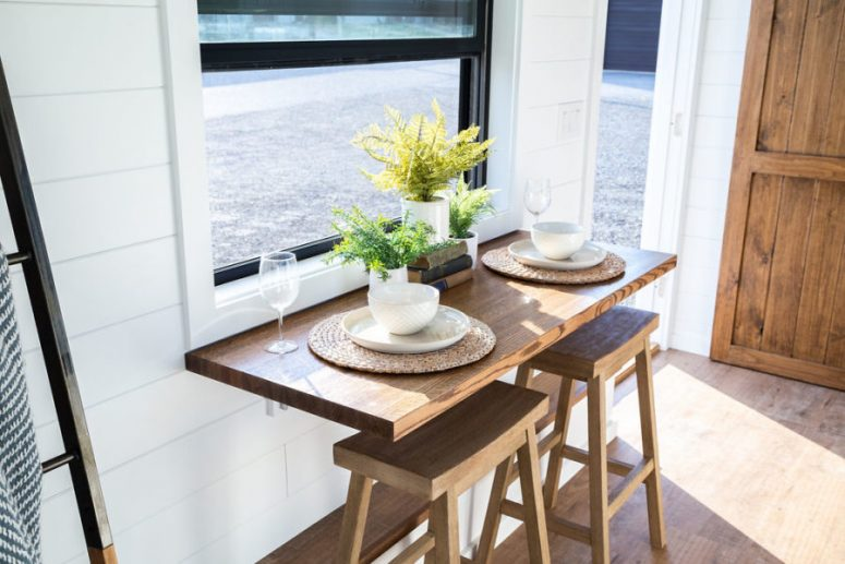 The dining space is done with a gold-down table and stools, the table is next to the window