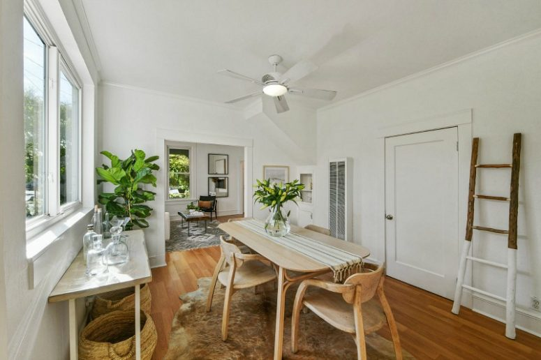 The dining space shows off a wooden dining set, a console, some baskets and statement plants