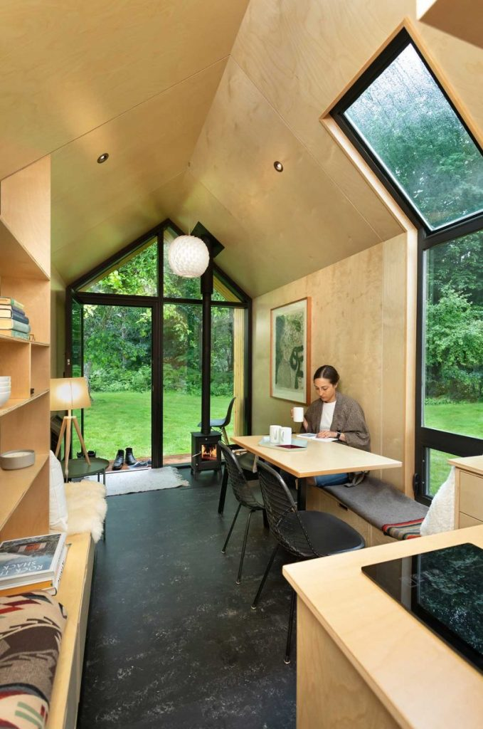 The inside of the house is done with light-colored plywoood and enjoys much natural light