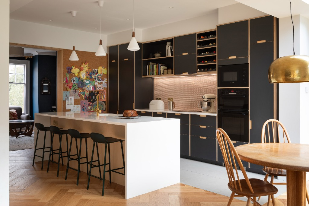 The kitchen features black cabinetry and pink tiles plus pendant lamps