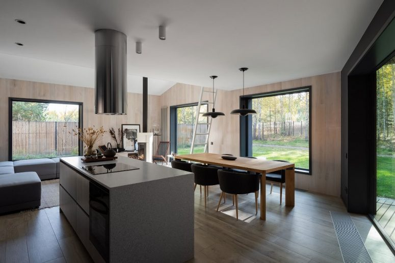The main space is comprised of three parts - a kitchen, a dining room and a sitting zone, with stylish minimalist furniture and gorgeous unbstructed views
