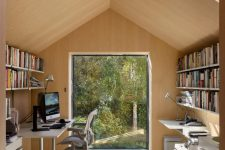 04 There's a home office with a large window and a skylight, with comfy furniture and open shelves