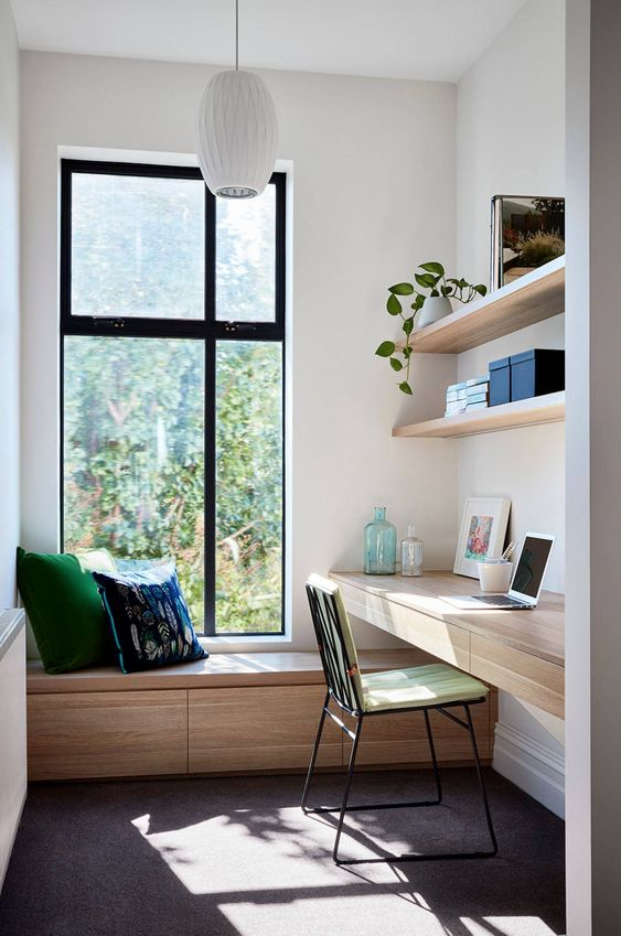 a minimalist home office with a floating desk and a daybed by the window, with open shelves and a comfy chair