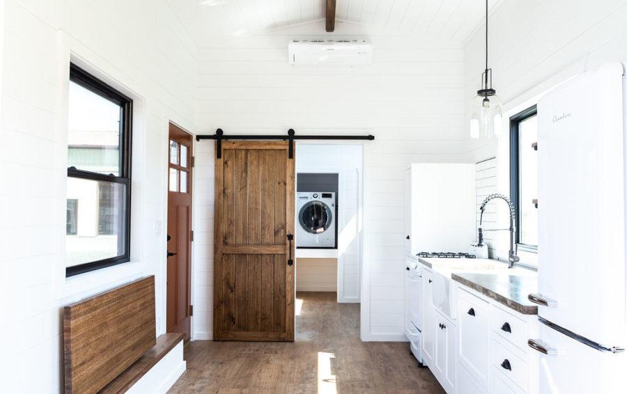 The bathroom is hidden behind a wooden barn door that's both beautiful and space efficient