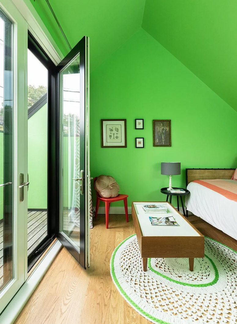 The bedroom is also done with bold green walls and a ceiling, stylish mid-century modern furniture and there's an access to the terrace