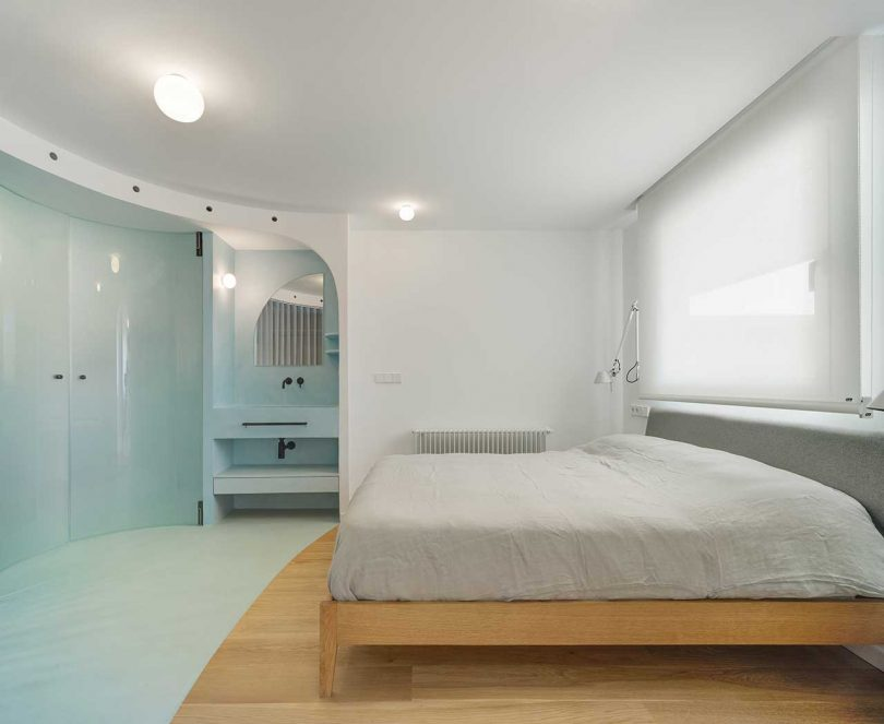 The bedroom shows off a wooden bed and sconces and the part of the room is taken curved blue doors to the bathroom