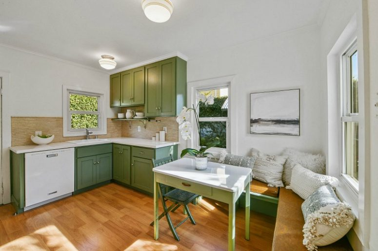 The kitchen is done with green cabinets and a table, with a corner seating and lots of pillows