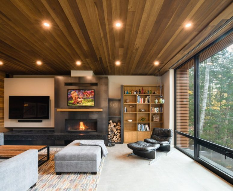 The living room shows off a built-in fireplace, upholstered and leather furniture, lights and a bright rug