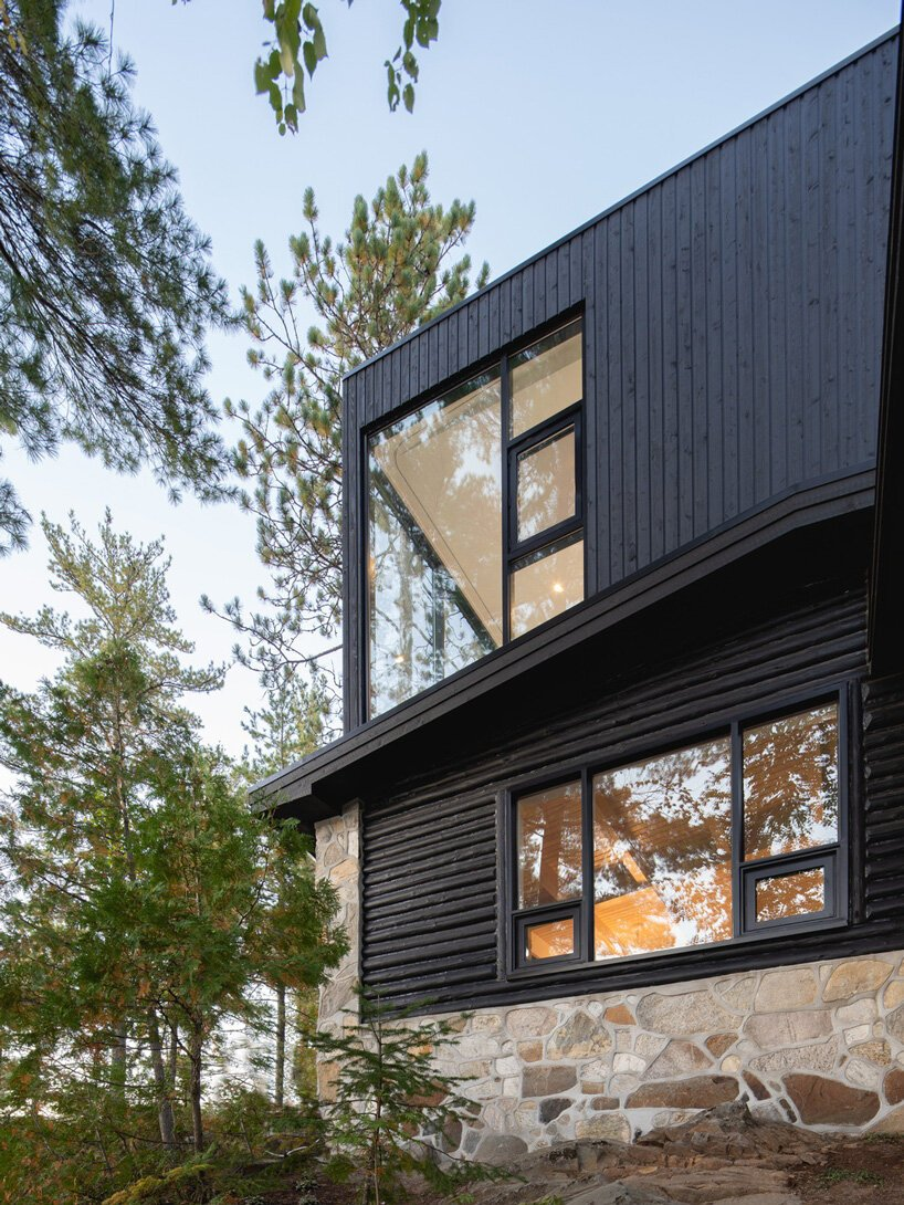 The old rustic log cabin was extended with a more modern part clad with black timber to match