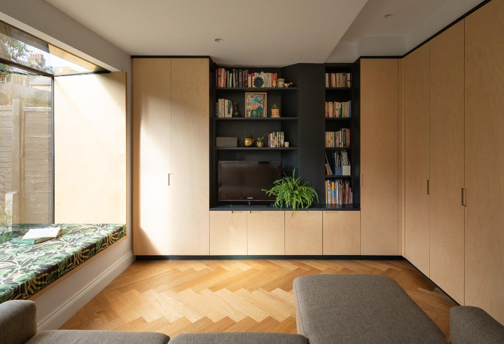 The sitting area is done with a windowsill daybed, a grey sectional and soem sleek storage cabinets