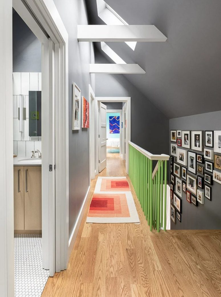 The foyer features skylights to illuminate it, there's a large gallery wall and a staircase with pretty green touches