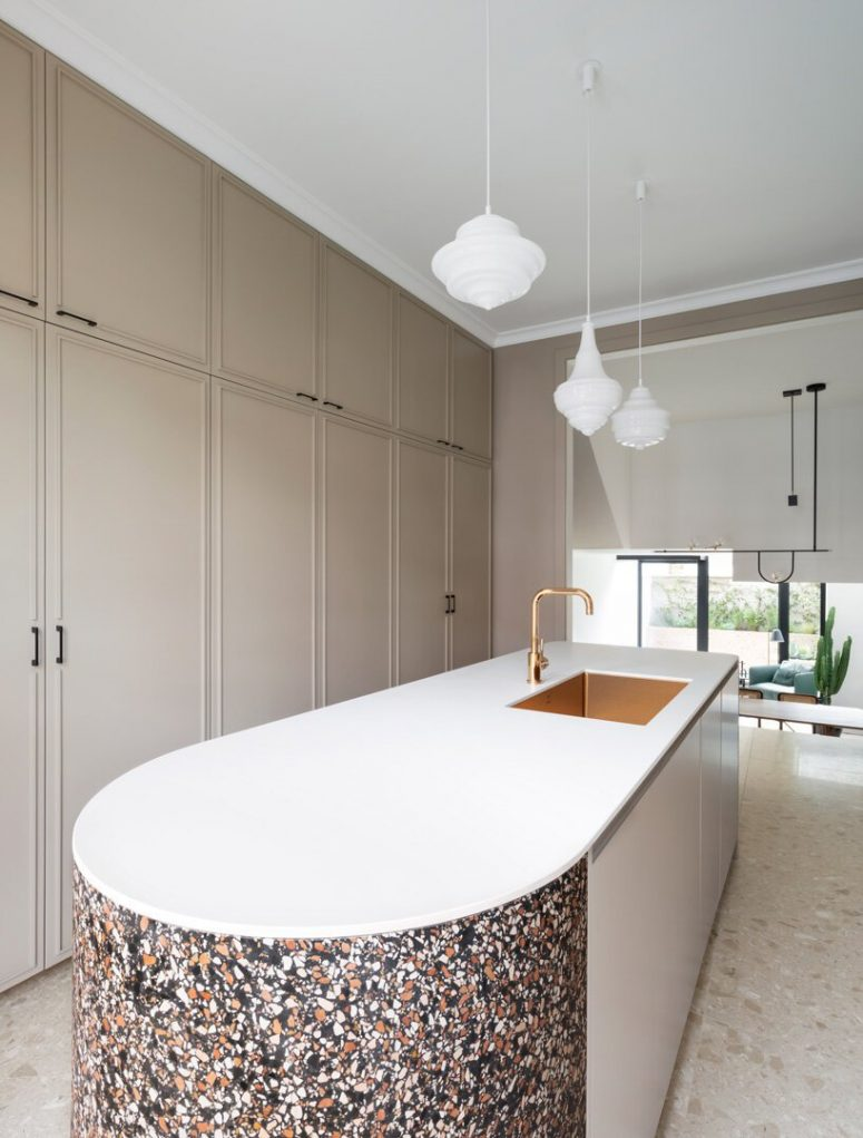 The kitchen is done with tan sleek cabinets that are built-in and are fully closed, while a large curved kitchen island makes a statement with its terrazzo part