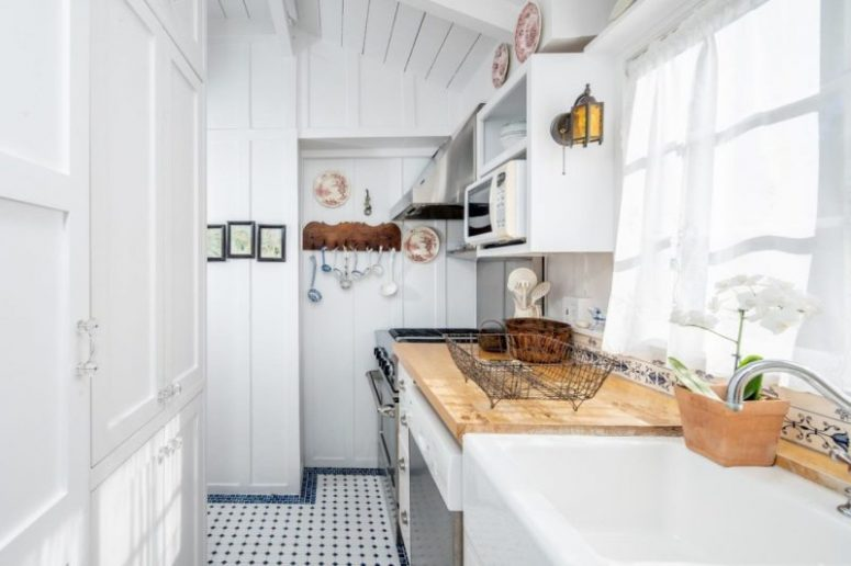The kitchen is white, with a wooden countertop, a printed tile floor and it's small yet cozy
