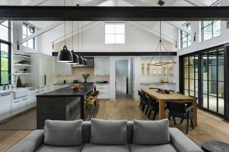 The kitchen island and dining table are parallel to one another and complement each other seamlessly
