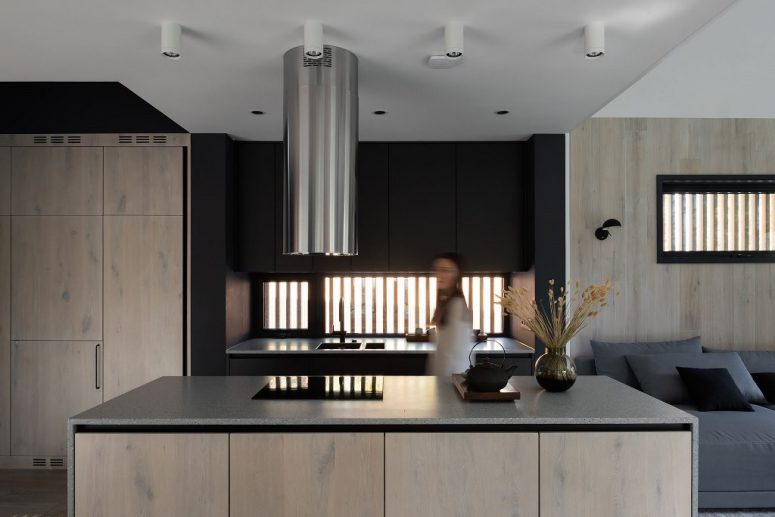 The kitchen shows off neutral wooden cabinetry and some black cabinets, too