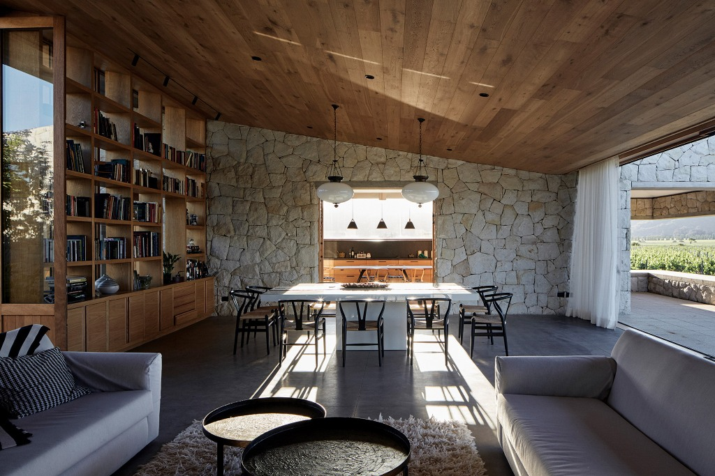The materials and colors inside are the same as outside - stone, wood and metal, there's comfortable furniture and large open bookcases