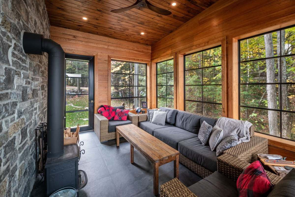 There's a covered porch with woven furniture, chic textiles and a hearth plus lights