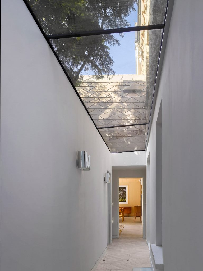A glass roofed corridor links the extension with the front of the house