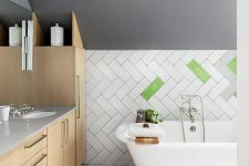 07 The bathroom is eye-catchy, with grey walls, boldly clad tiles, penny tiles on the floor, sleek plywood cabinetry and a vintage tub