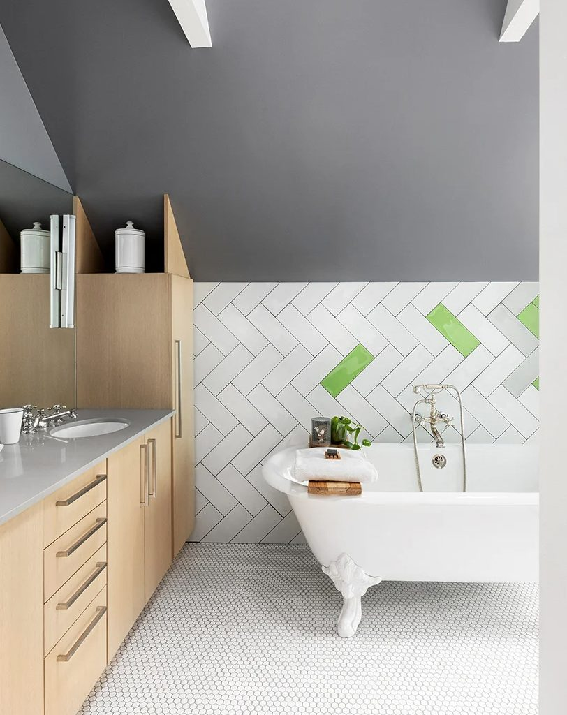 The bathroom is eye catchy, with grey walls, boldly clad tiles, penny tiles on the floor, sleek plywood cabinetry and a vintage tub