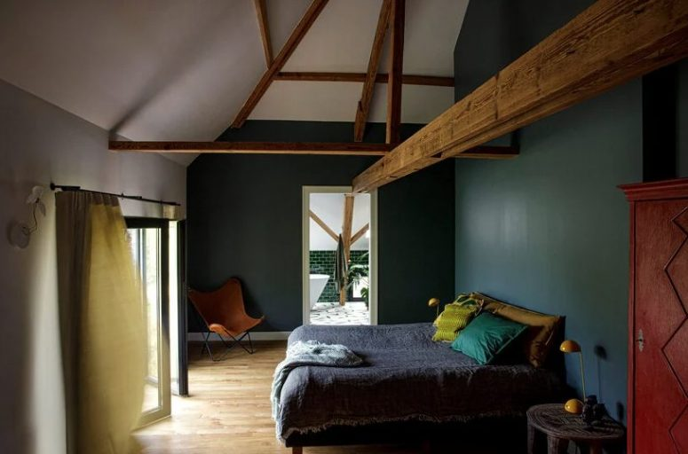 The bedroom is moody, with hunter green walls, bright textiles, wooen beams that add charm and a vintage feel