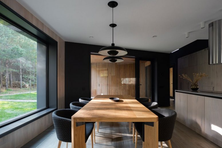The dining zone is done with a wooden table, black chairs and some pendant lamps over the table