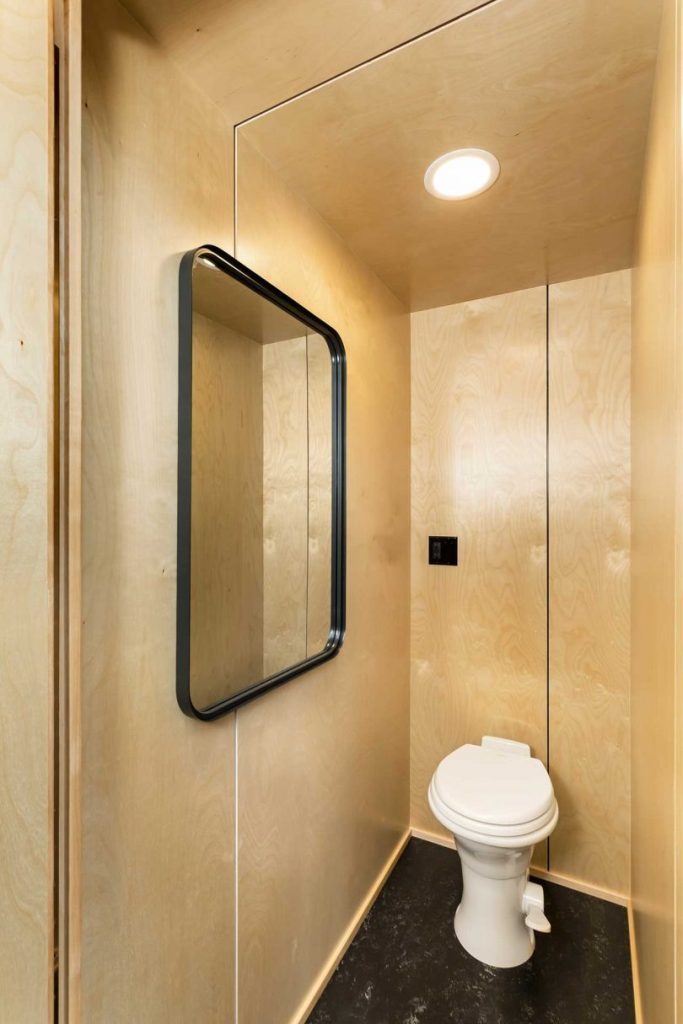 The toilet is small, with a large mirror and everything here is clad with the same plywood