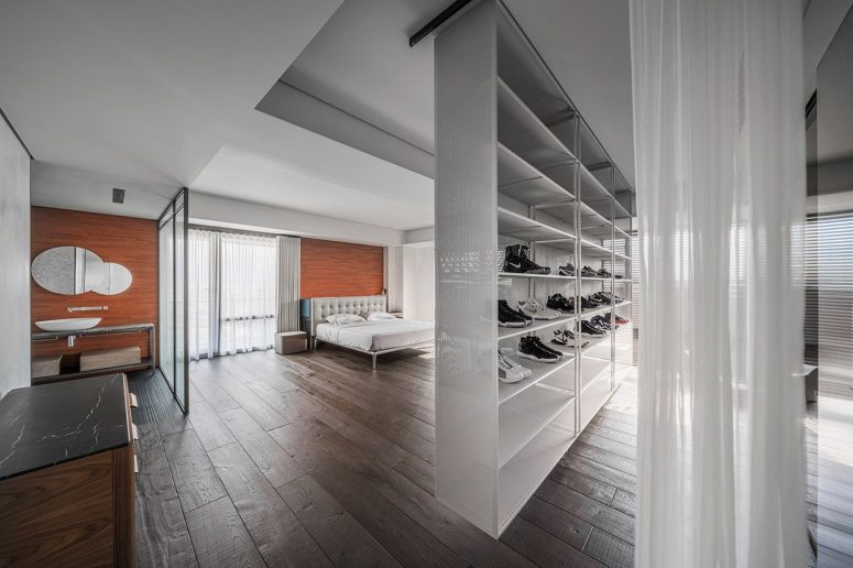 Another bedroom is also combined with a bathroom, and a wall with trainers is a space divider