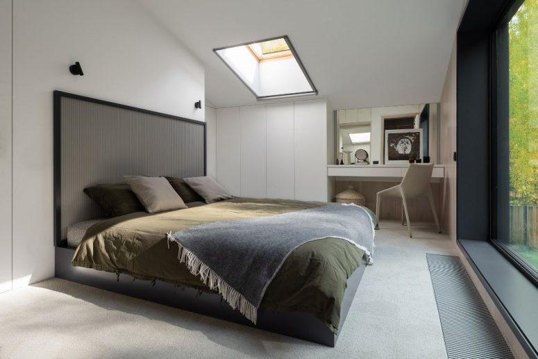The bedroom shows off a large and comfy bed, a cozy nook and sleek storage, a skylight and cool artworks