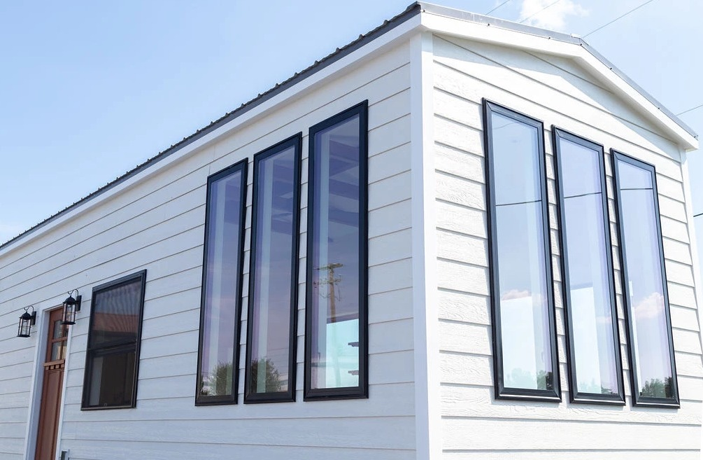 The tall vertical windows are paired in sets of three on this side which gives this tiny house a distinguished look