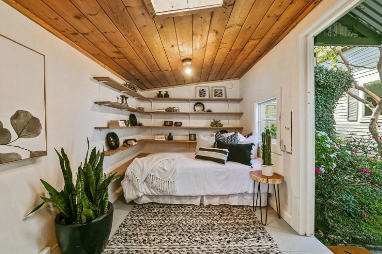 The guest cottage features a modern boho bedroom with floating shelves, some potted plants and a wooden ceiling