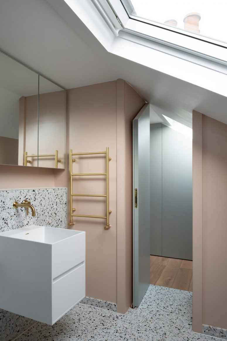The second bathroom shows off neutral terrazzo, a floating sink and blush walls