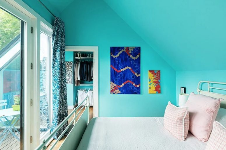 This cozy bedroom is done with bright turquoise walls and a ceiling, a metal bed and bold art, there's an access to a small clsoet