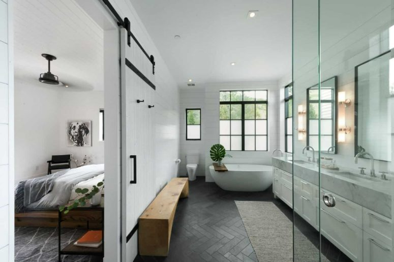 The master suite has a large and stylish bathroom with large windows and a sliding barn door