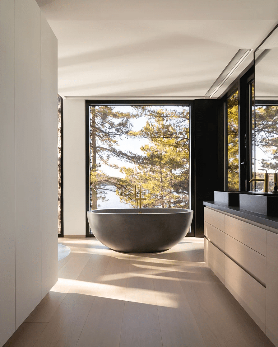 The minimalist bathroom features several windows to have amazign views of the lake