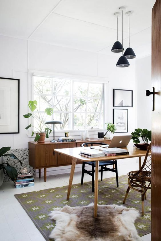 a stylish mid-century modern home office with windows and a cluster of pendant lamps is a cool and airy space