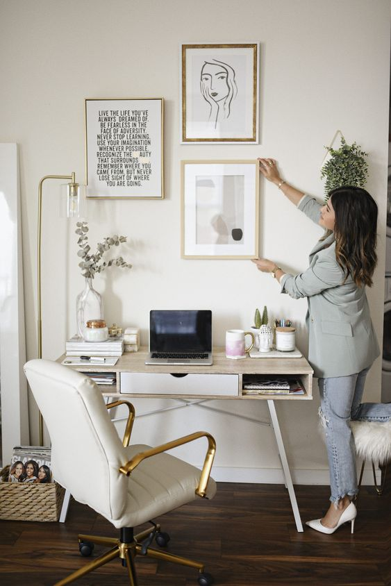 a neutral home office personalized with a gallery wall and with some greenery around